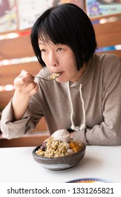 Asian woman eat shaved ice at a store