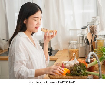 asian woman eating bread while preparing food in the kitchen