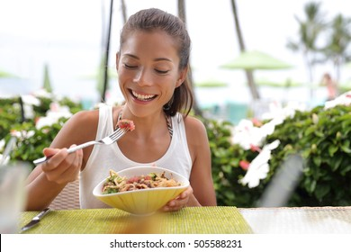 Asian woman eating a fresh raw tuna dish, hawaiian local food poke bowl, at outdoor restaurant table during summer travel vacation. Hawaii poke bowl food plate. Ahi tuna hawaiian cuisine.
