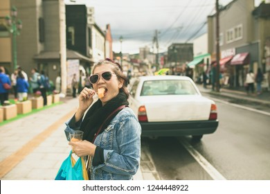 asian woman eating hokkaido melon on otaru street one of most popular traveling destination in hokkaido japan