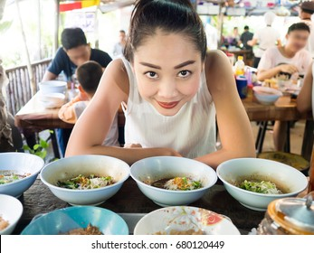 Asian woman eating noodle in Thai local restaurant in Thailand.