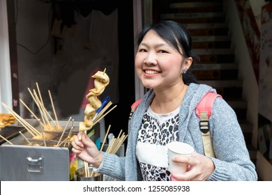 Asian woman eating South Korea street food, Korea local food oden fish cake it is famous in Street food in Seoul, South Korea