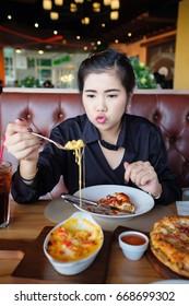 Asian woman eating spaghetti in restaurant