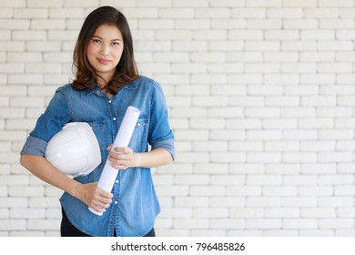 Asian woman engineer in blue jeans shirt carrying paper roll standing in front of brick wall, holding white safty helmet in self confident manner