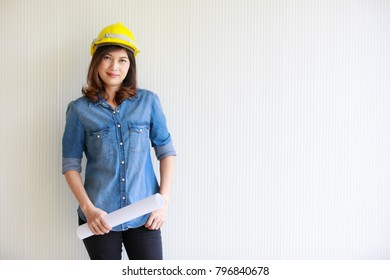 Asian woman engineer in blue jeans shirt wearing yellow helmet and carrying paper roll looking at camera, in front of beautiful pattern wall