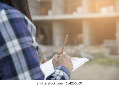 Asian Woman engineer checklist in front of construction site.Professional Architect writing and  inspect or fill out form at building project with better structures.Engineer,architect inspect concept