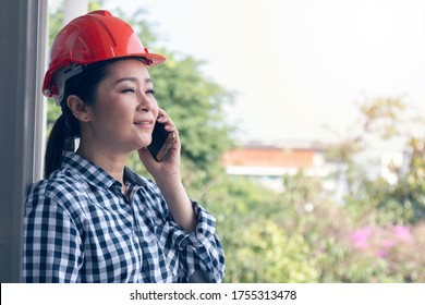 Asian woman engineer talking on mobile phone in building site.