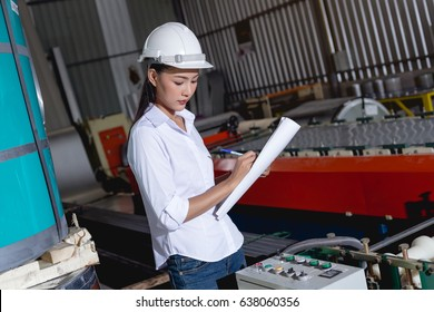 Asian woman engineer working on blueprint in of a metal sheet roof. Machine with rolls.In the factory.