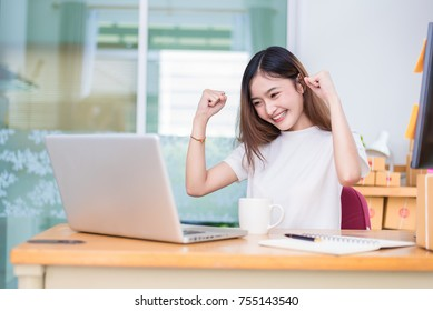 Asian woman enjoy herself while using laptops and internet in office. Business and marketing and part time concept. On line shopping and business success theme. Happy mood when finished working job.