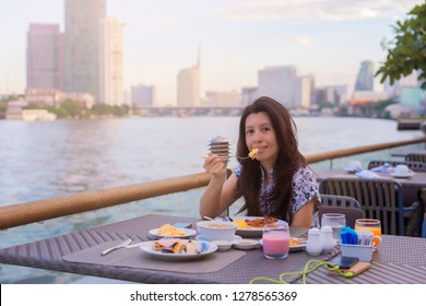 Asian woman enjoying breakfast with beautiful view from terrace at the hotel and looking at camera. Breakfast on the hotel restaurant porch.