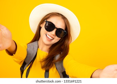 Asian Woman enjoying the selfie with herself isolated on yellow background summer travel concept.