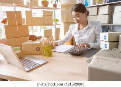Asian woman entrepreneur using calculator with pencil in her hand, calculating financial expense at home office,online market packing box delivery,Startup successful small business owner,SME, concept