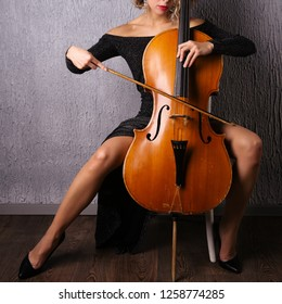 asian woman in an evening dress playing the cello.
