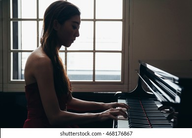 Asian woman in evening dress playing piano in window background in silhouette (Intention to make subject dark)