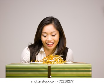 An Asian woman is excited to receive a gift