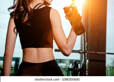 Asian woman exercising in the gym, Young woman workout in fitness for her healthy and office girl lifestyle. she is drinking a protein shake.