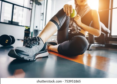 Asian woman exercising in the gym, Young woman workout in fitness for her healthy and office girl lifestyle. She is holding green apple.