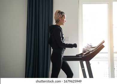 Asian woman exercising on treadmill home gym