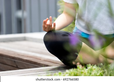 Asian woman exercising and sitting in yoga lotus position in garden