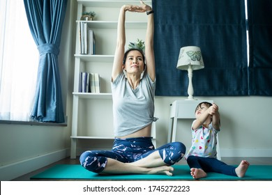 Asian woman exercising yoga works out at home. Two young little girl and baby playing together around mother. Cute daughters crawling having fun and laugh with smile. Children, parent activity concept