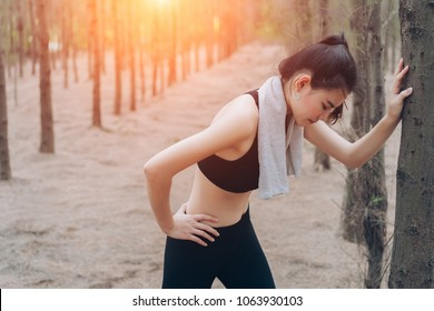 Asian woman exhausted or tired after training workout at forest nature in the morning with cardio runner marathon,run out of energy healthy lifestyle.