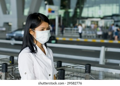 asian woman with face mask in front of the international airport in bangkok