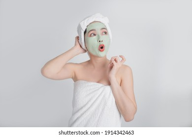 Asian woman face masks green cream on white background. She was happy and surprised.