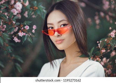 Asian woman fashion close-up portrait. Beautiful mixed race asian caucasian young girl perfect skin creartive art make-up wearing red sunglasses trendy white japanese kimono standing agaist flower