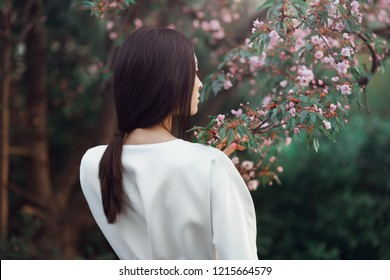 Asian woman fashion close-up portrait. Beautiful mixed race asian caucasian young girl wearing trendy white japanese kimono standing agaist flower background. Spring blossom of sakura tree in city