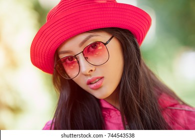 Asian woman fashion close-up portrait. Beautiful mixed race asian caucasian young girl in pink hat jaket and red sunglasses looking at camera outdoor against green blurred bokeh nature background