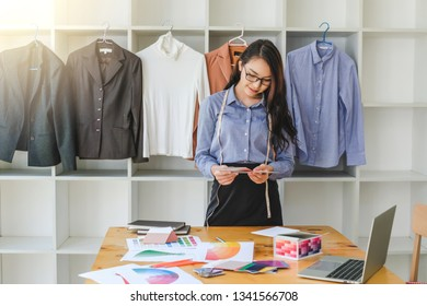 Asian woman fashion designer work at home happily.
