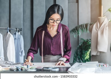 Asian woman fashion designer working on her model in showroom