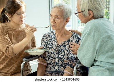 Asian woman feeding tired senior patient,anorexia,eat less food,depressed female elderly suffer from depressive disorder,symptoms of depression,loss of appetite,insomnia, bored of food in old people