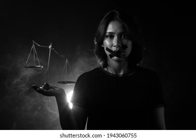 Asian Woman feel injustice, insecure and corruption in society So she closes Mouth with duck tape and show unbalance balance scale, Concept not to say a word. Dark tone environment copy space