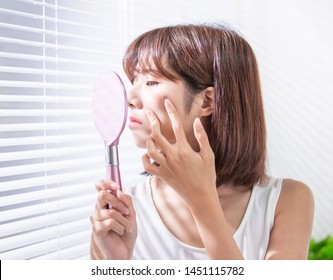 asian woman feel sad because her skin has acne prone