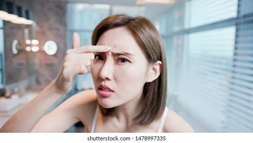 asian woman feel sad because her skin is very oily on face