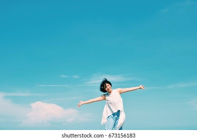 Asian woman feeling excited standing in front of blue sky background,copy space