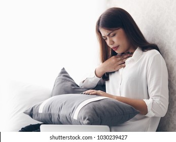 Asian woman feeling unwell with sore throat,during she working with tablet at home.