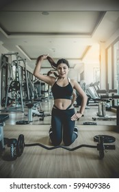 Asian woman fitness girl sit prepare for lift up barbells