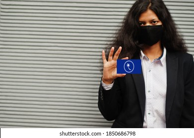 Asian woman at formal wear and black protect face mask hold Chuuk State flag at hand against gray background. Coronavirus at country concept.
