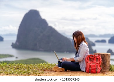 Asian woman freelancer working with technology laptop with happiness action at Fantastic Landscape of samed nang chee view point, Freelance working and travel anywhere concept