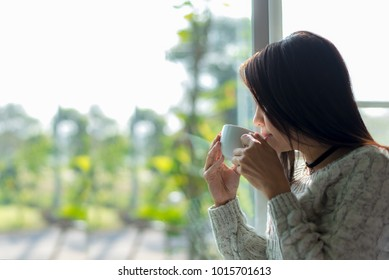 Asian woman fresh morning drinking coffee and looking out of the window on sunny day. Copy Space.  Lifestyle Concept.