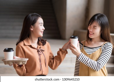 asian woman friend sharing coffee; portrait of two friendly woman giving coffee, concept of friendship, sharing; young adult asian woman model