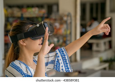 Asian woman getting experience using VR-headset glasses of virtual reality.
