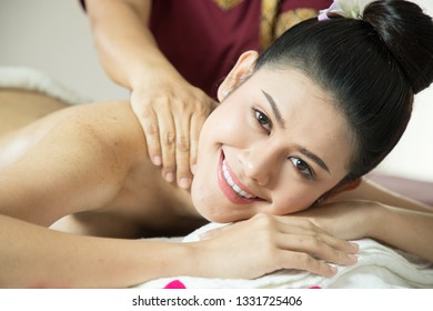 Asian woman getting thai herbal compress massage in spa