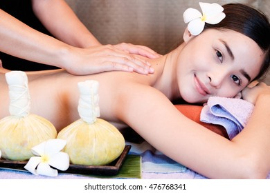 Asian woman getting thai herbal compress massage in spa.She is very relaxed.Portrait of young beautiful woman in spa environment