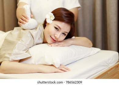 Asian woman getting Thai herbal hot compress massage in spa . She is happy and smiling.