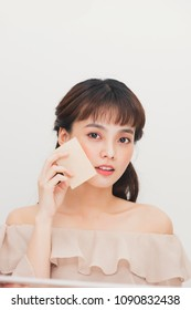 Asian woman girl removing oil from face using blotting papers