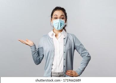 Asiatische Frau in Brille und Gesichtsmaske stellt neues Firmenprodukt oder Firmenbanner vor, zeigt und hält Werbematerial auf der linken Seite über dem Kopienraum
