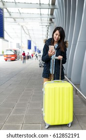 Asian woman go travel and using mobile phone with suit case at airport
